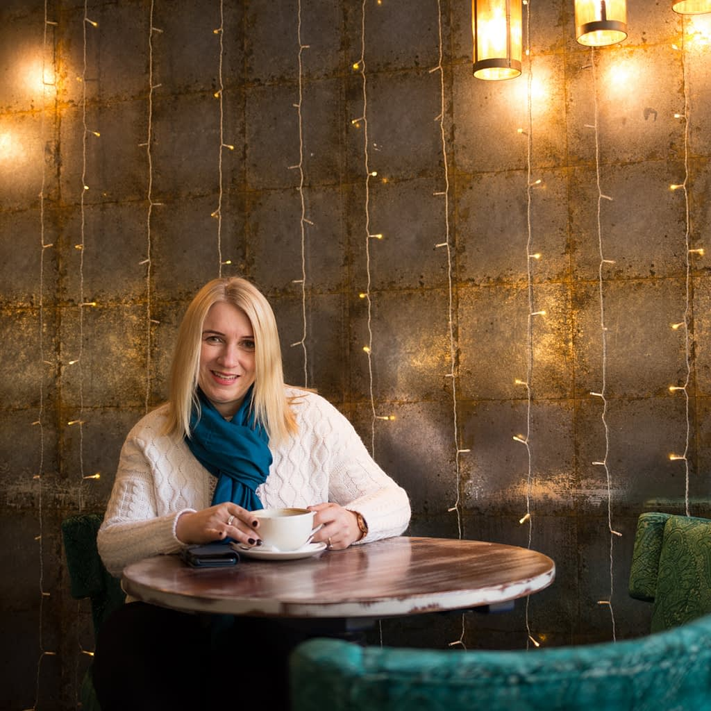 Catherine Tuckwell Personal Brand Photography session in restaurant with green chair and string lights backdrop
