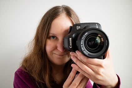 Catherine Tuckwell Personal Brand Photography holding camera to eye while smiling against white background