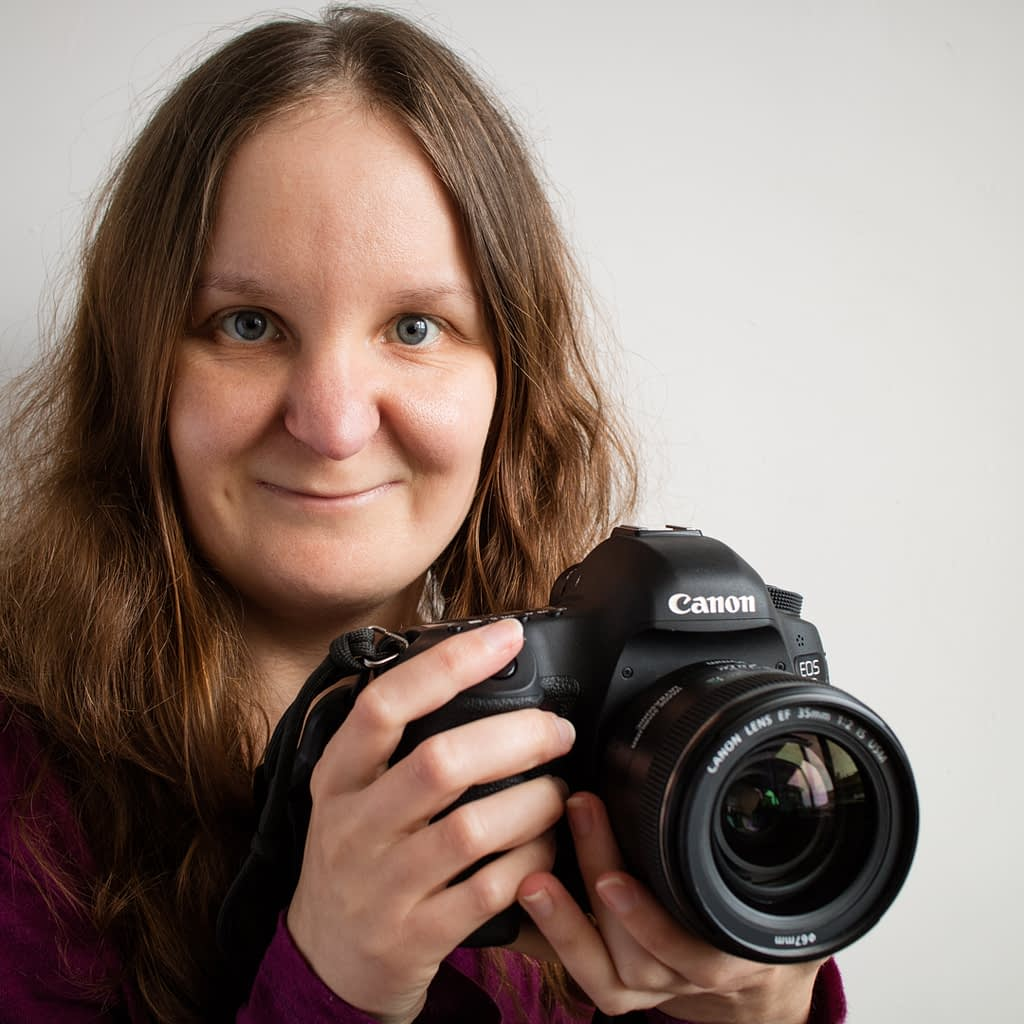 Catherine Tuckwell Personal Brand Photography headshot smiling with camera against white background