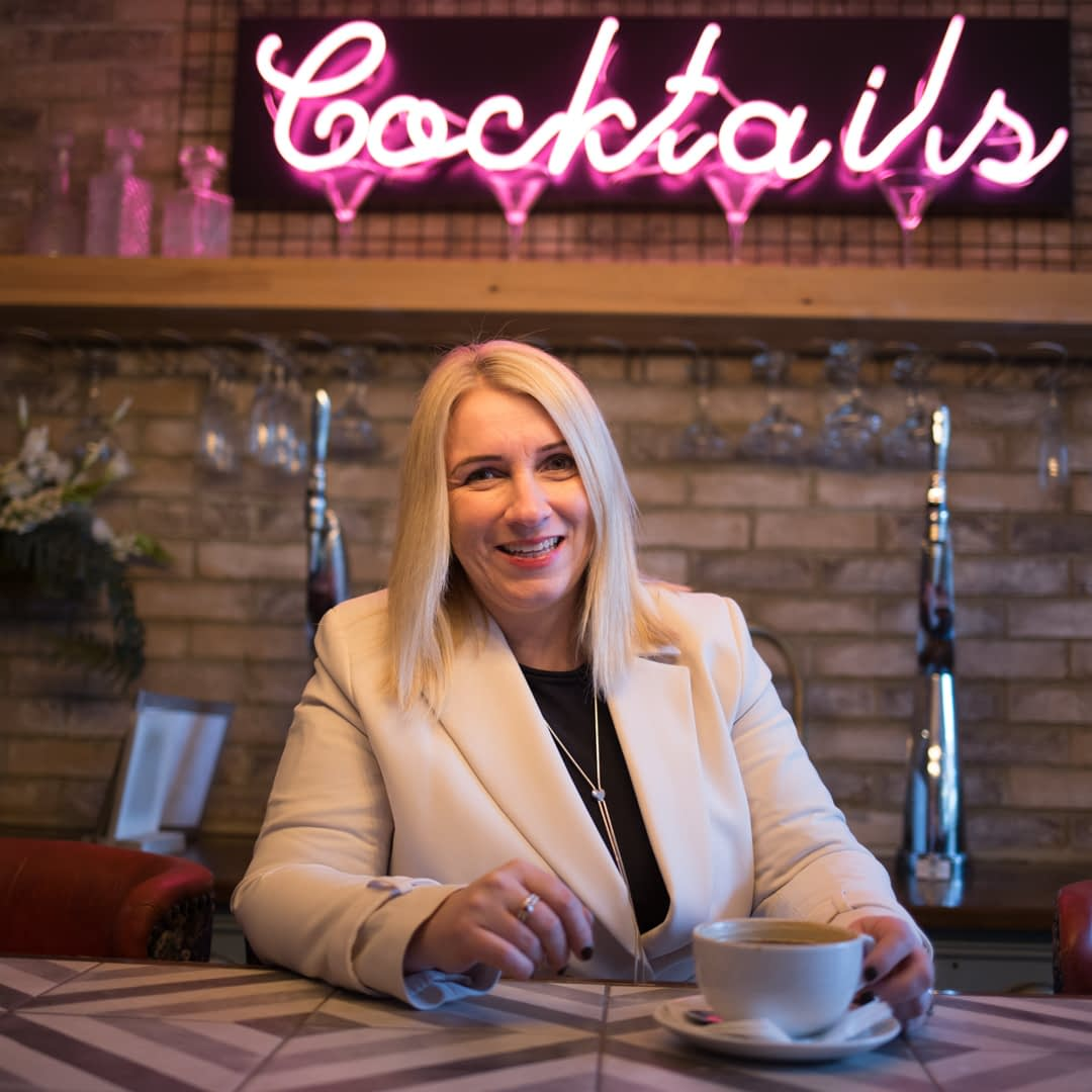 Catherine Tuckwell Personal Brand Photography session in restaurant with neon Cocktails sign