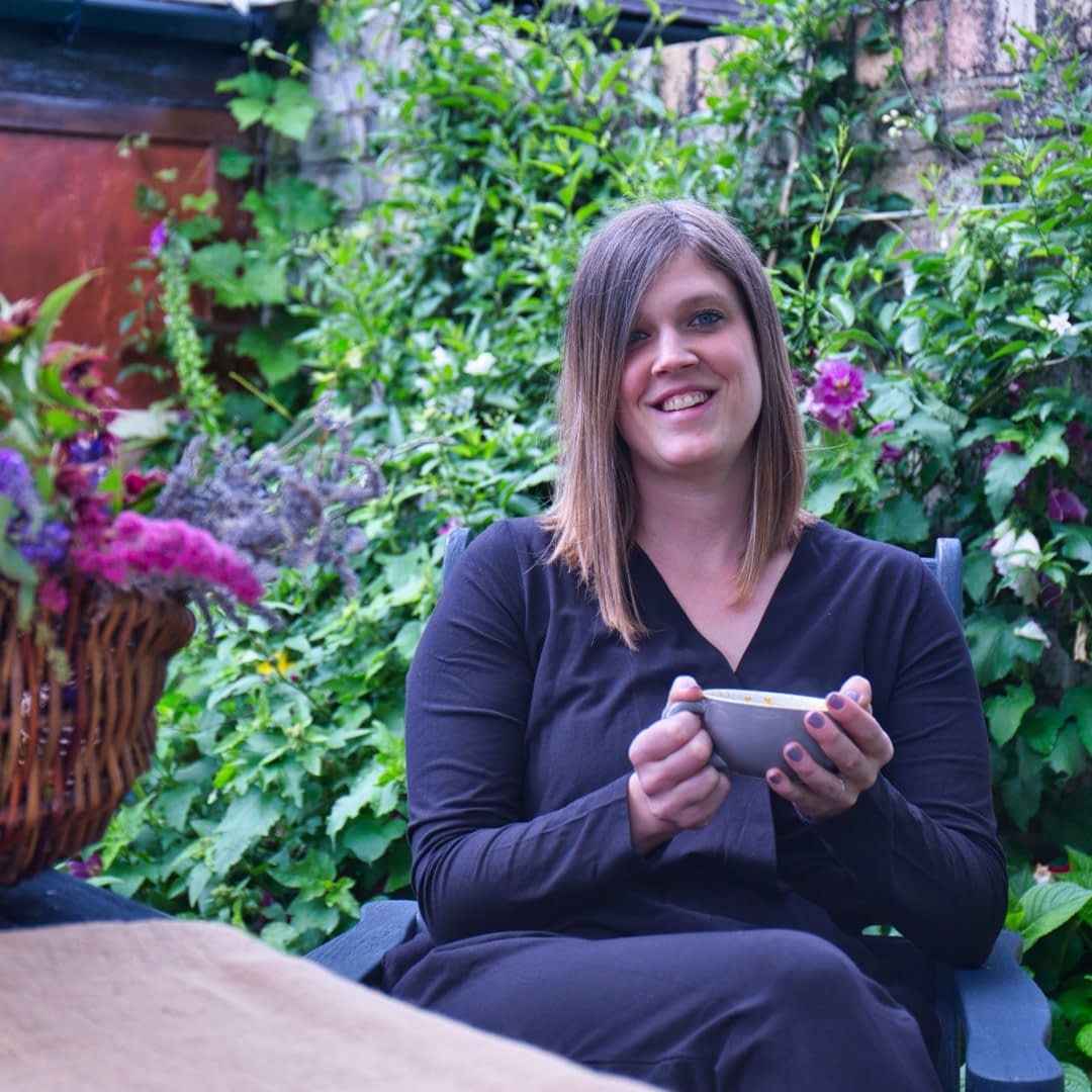Catherine Tuckwell Personal Brand Photography session relaxing in garden with coffee mug and flowers